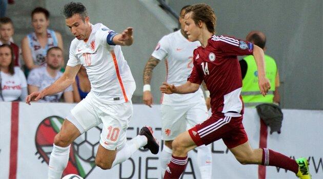 Robin Van Persie în duel cu Janis Ikaunieks în meciul Letonia - Olanda 0-2